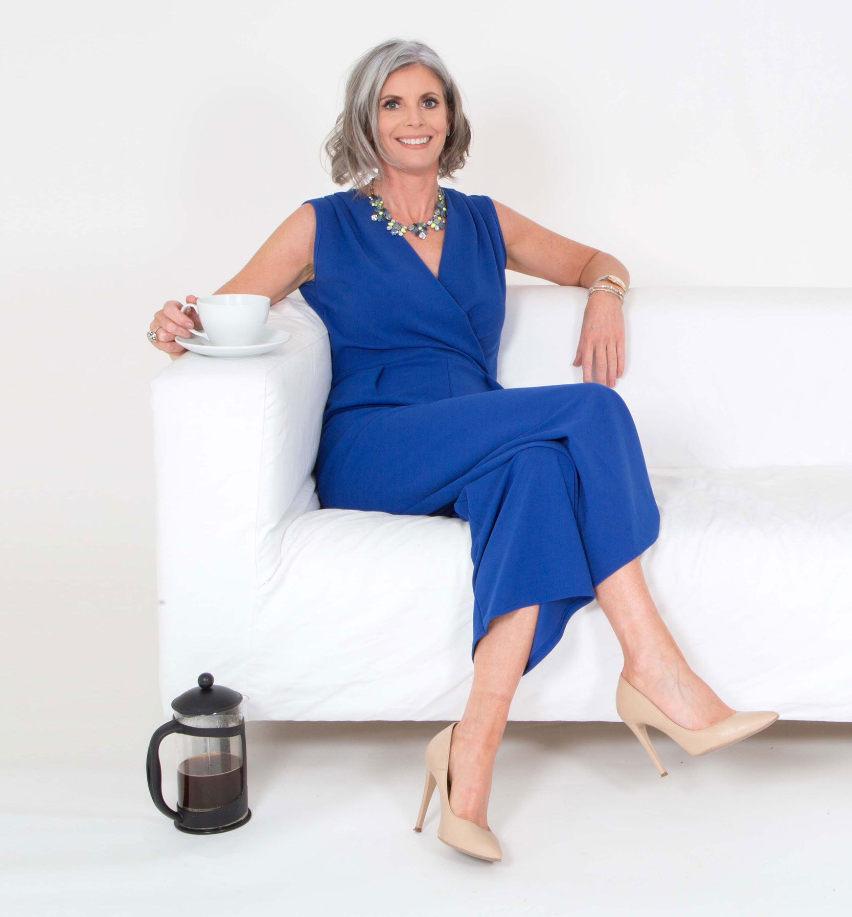 Bernie Delaney - sitting on a couch wearing a blight blue dress